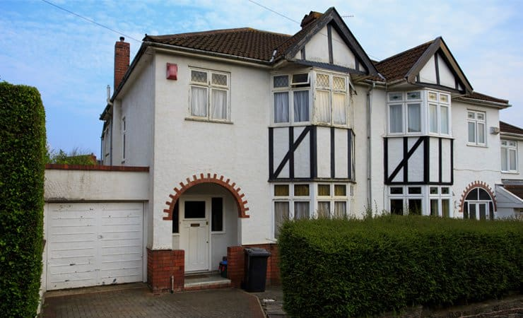 Photograph of a typical 1930s semi-detatched house with bay windows and a tall chimney. Photograph taken in Bristol, UK