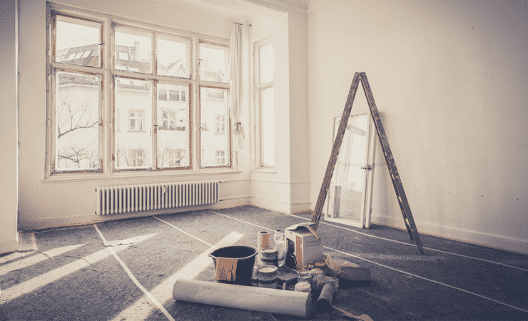 A photo of a living room being refurbished. A ladder stands near some windows and tools and pots of paint are on the floor.
