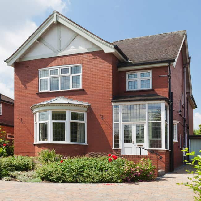 A photograph of a traditional red-brick English detached house