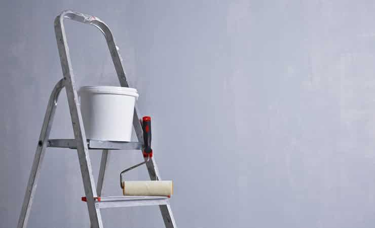 A photo of a paint pot and a roller on a ladder