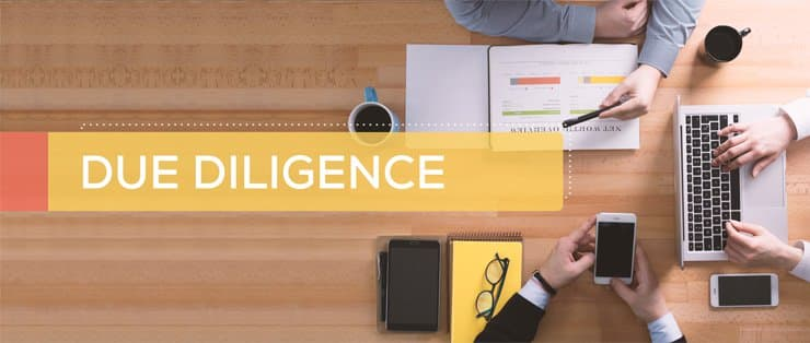 A desk with 3 people sitting around it with paperwork. The words 'due diligence' are written across the desk