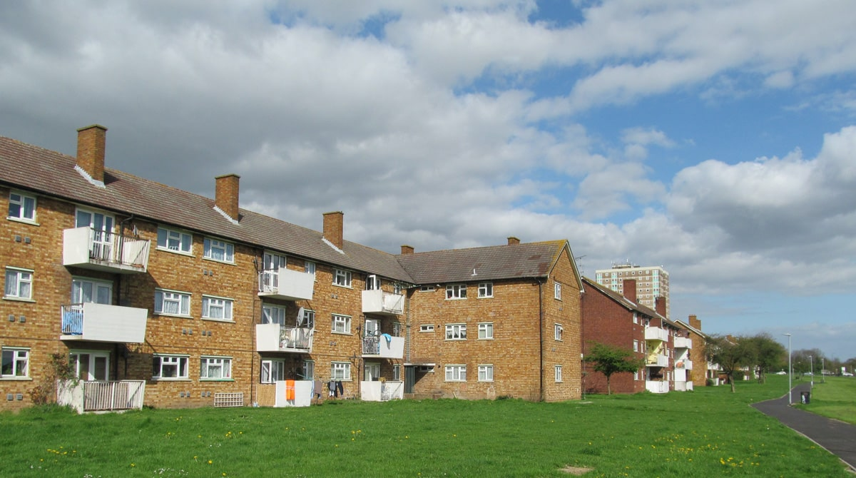 Three story 1950s council flats in white and exposed brick on the Marks Gate Estate in Dagenham