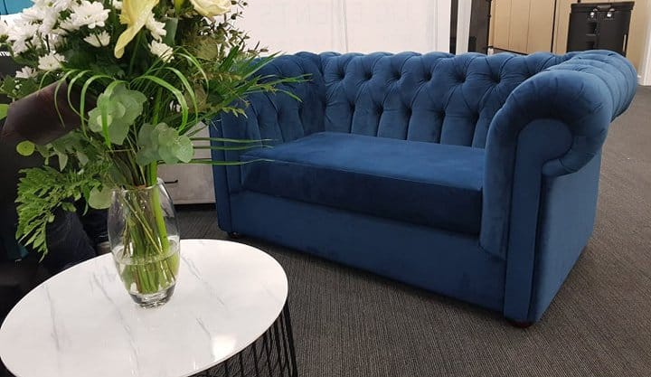 Photograph of a blue Chesterfield sofa with flowers in the foreground