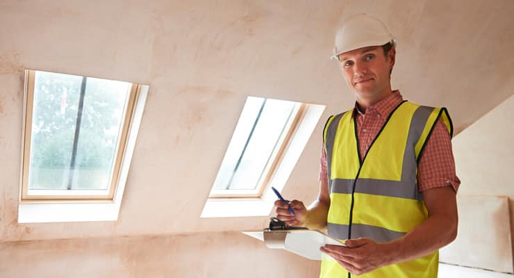A building inspector wearing a high-vis vest and hard hat inspects a new-build property