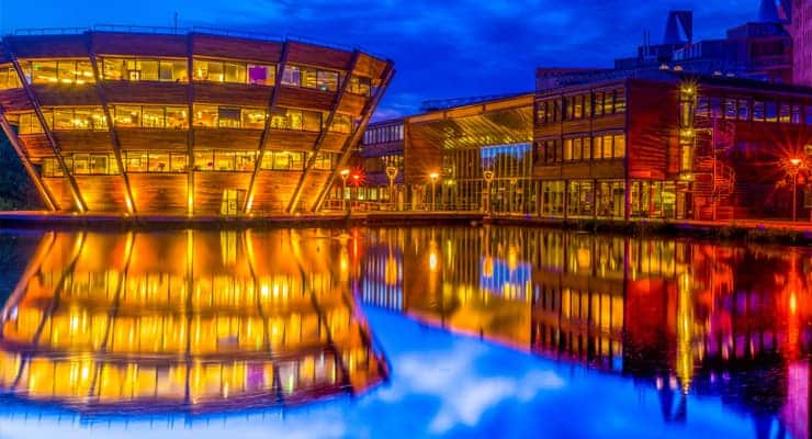 A photograph of the Jubilee Campus in Nottingham at night, reflected in the water.