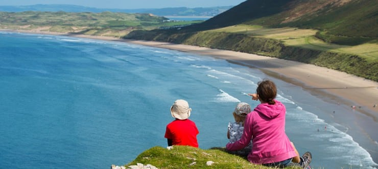 A family of two young children and they mother look out from a cliff top across Rhossili Bay