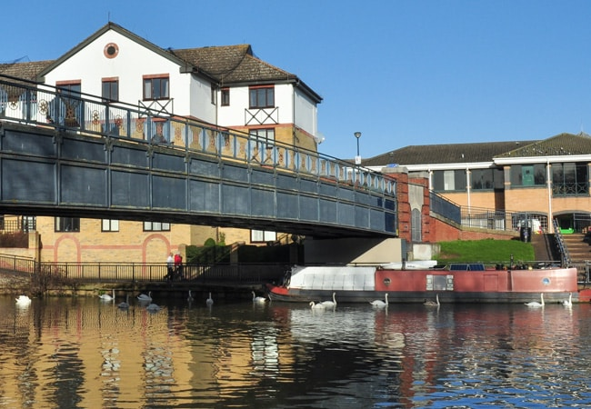 A footbridge over a river on a summer day. Photograph of a bridge over the River Nene in Peterbourough