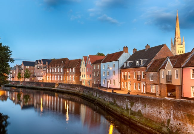 Colourful and historic town houses sit on the quayside in Norwich. Photograph taken at dusk