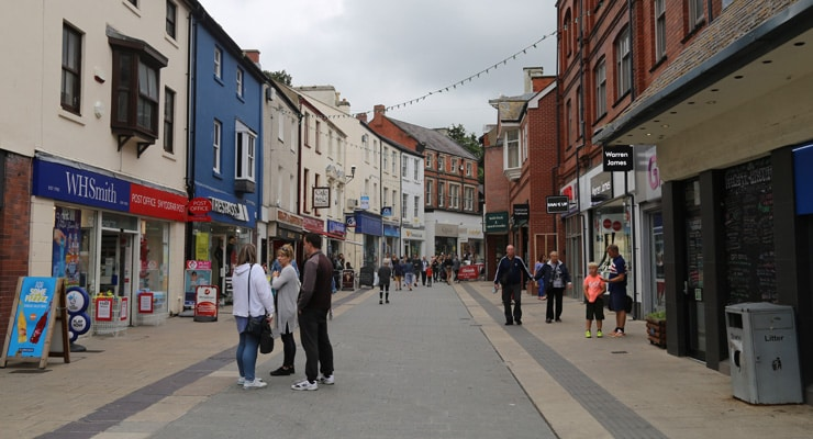 A pedestrianised high street in Bangor with shoppers and shops