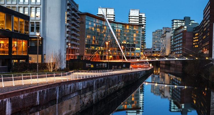 The urban landscape of Manchester at night along the banks of the River Irwell