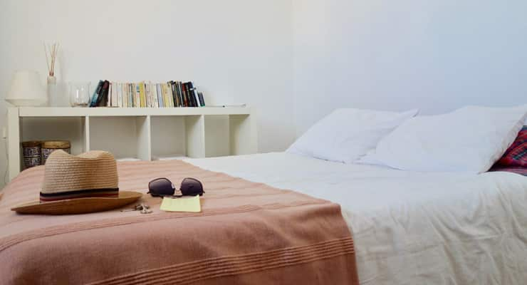 A hat rests on a bed with a brown and white bead spread. Style is reminiscent of an Airbnb listing