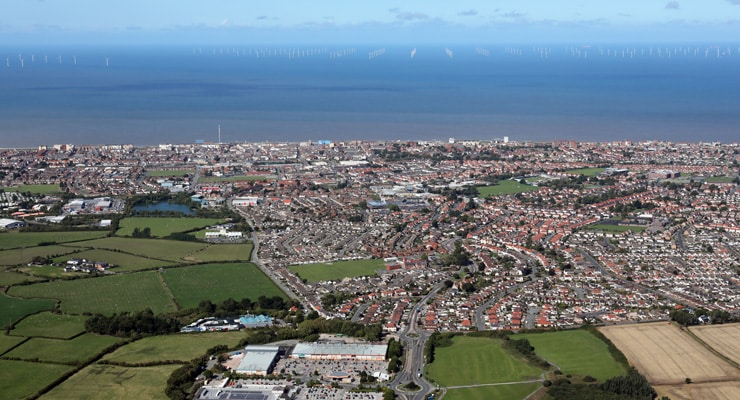 Aerial photograph of Rhyl, North Wales with the ocean and coastline visible and an off-shore wind farm in the distance