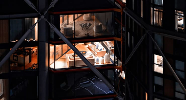 The outside of a tower block at night where interior luxury short term lets can be clearl;y seen through the windows