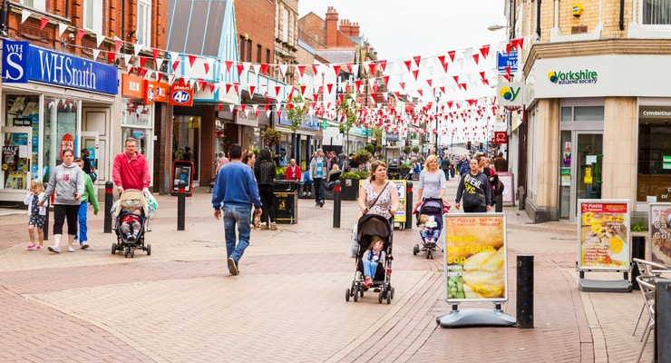 A busy shopping street decorated with bunting. Photo taken at the White Rose Centre, High St, Rhyl