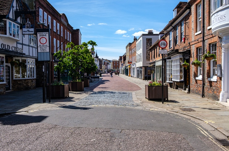 A mostly empty shopping street in the centre of Chichester on a summer day.