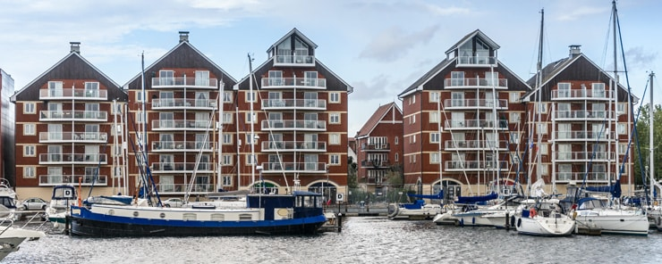 Blocks of flats on the Ipswich Waterfront, where house boats sit in the foreground.