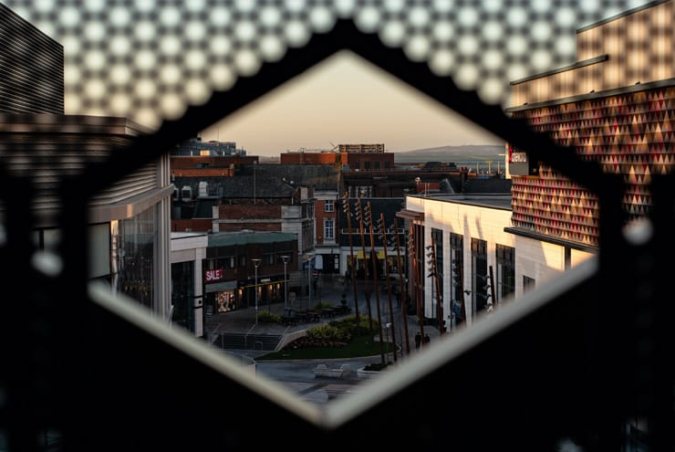 A shot of new developments in Warrington Town Centre. Photograph taken 'artistically' through a gap in a metal fence.