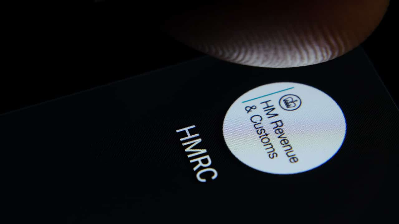 The HMRC logo can be seen on a phone screen, sitting next to a stone