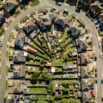 A bird's eye aerial view of a U-shaped street and suburban housing in Ipswich, UK