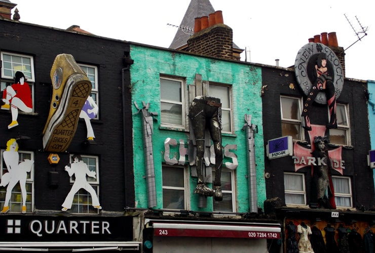 Artistic shop fronts in Camden Town. One shop has a giant boot hanging from it, the other a pair of trousers.