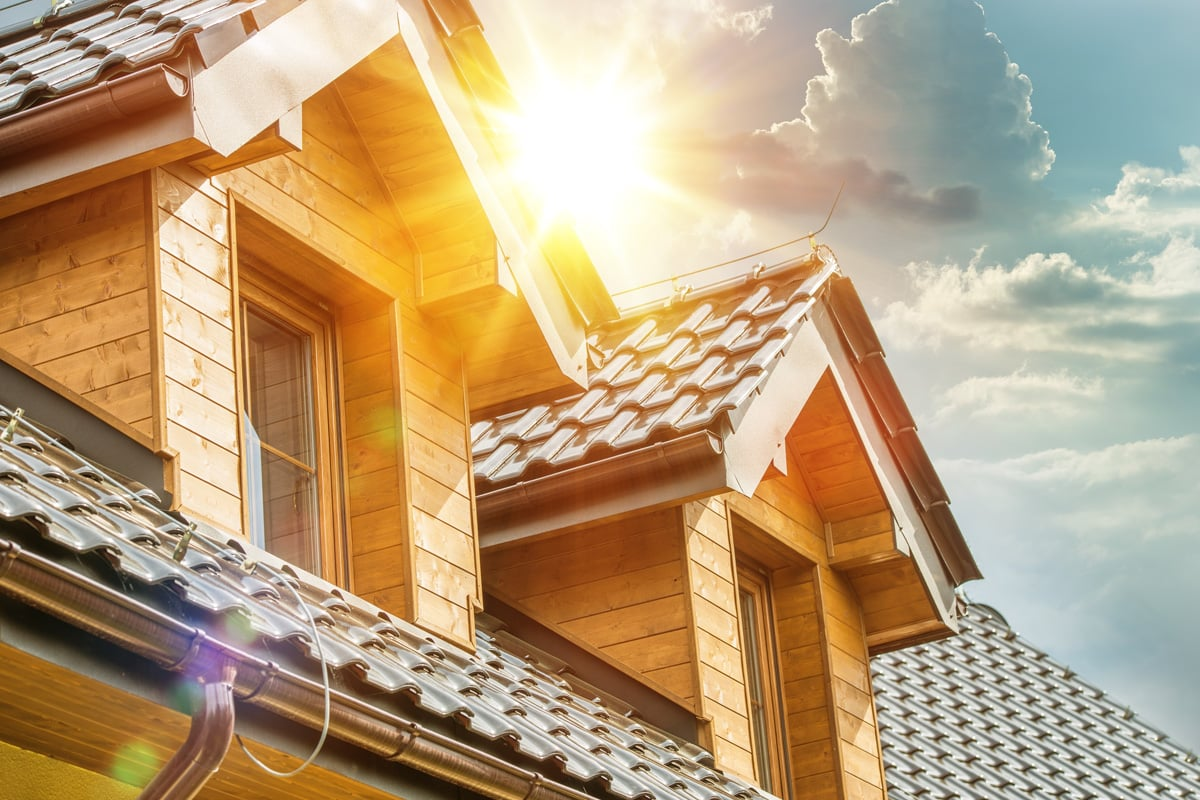 Sun breaks through clouds over a house roof and attic window. Picture represents a release of equity.