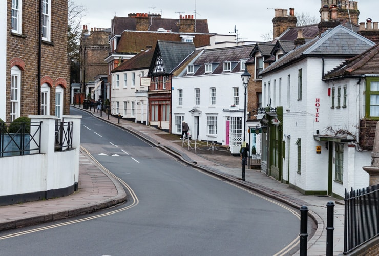 Traditional pubs, restaurants and shops on a sloping high street. Photograph taken in Harrow on the Hill in Harrow, West London.