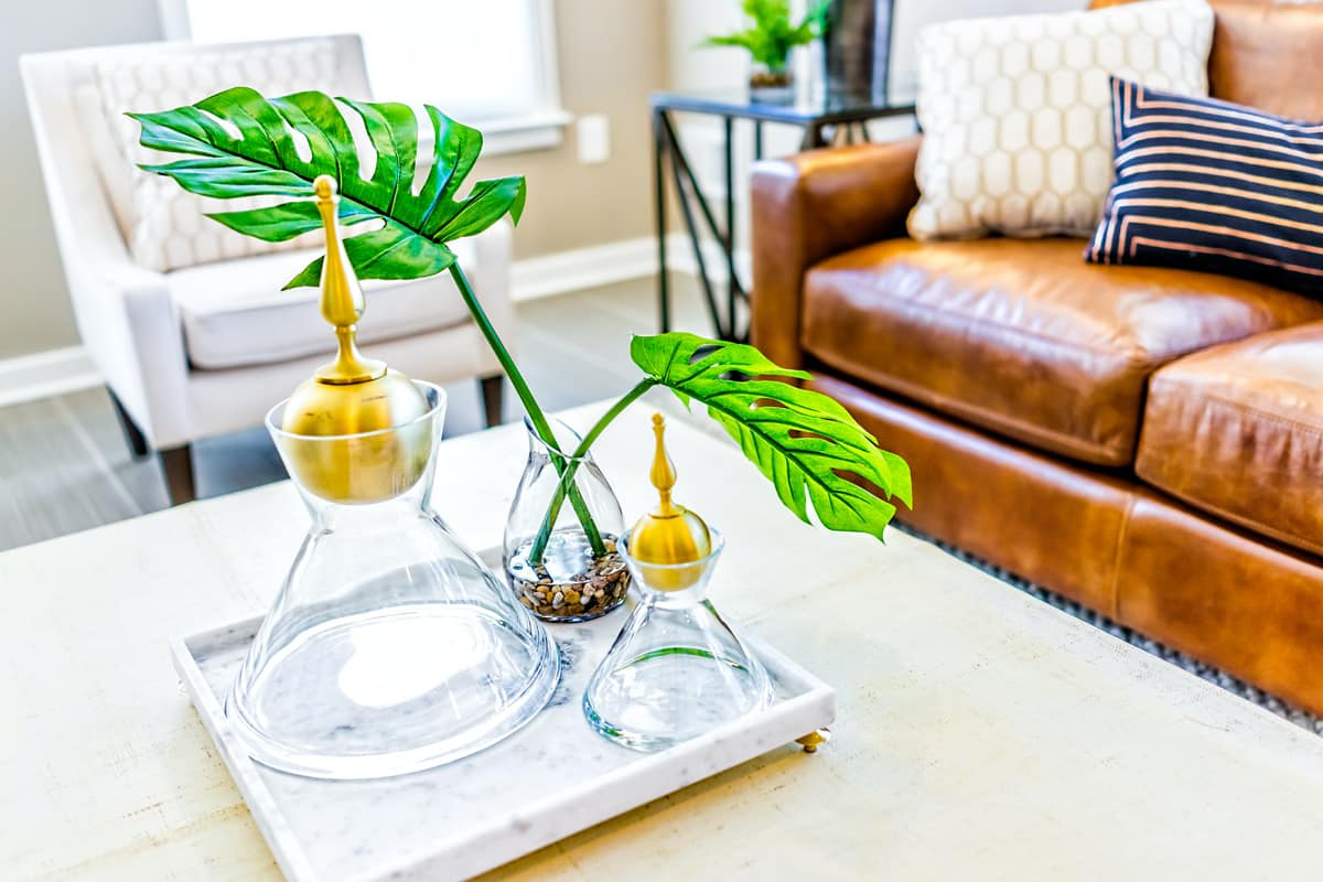 A closeup of serving tray stand with empty glasses and a plant in a home staging example.