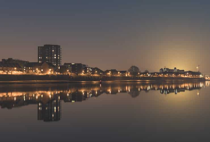 The lights of Fulham are reflected by the River Thames at night.