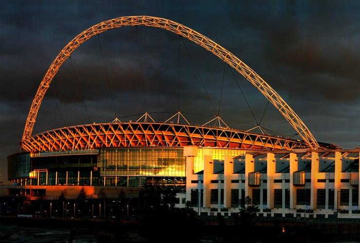 Wembley Stadium in Brent. Photograph taken at night with the stadium illuminated by upward facing lights.