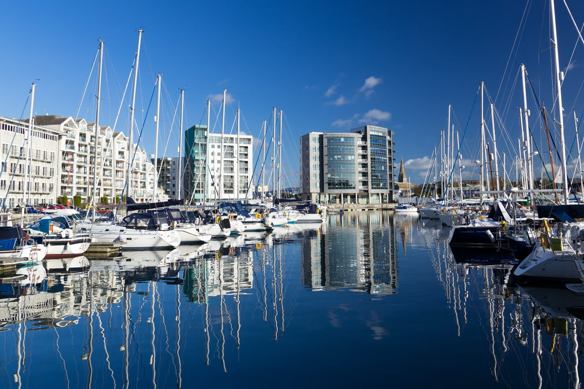 The marina in Plymouth with yachts along the waterfront and skyrise buildings in the background.