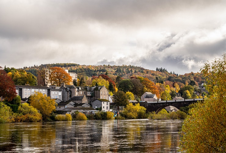 An autumnal scene of Perth in Scotland. The city is seen among red, yellow and orange trees.