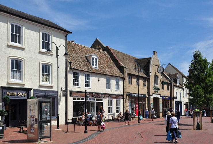 Shoppers walk about the marketplace in Ely on a bright sunny day.