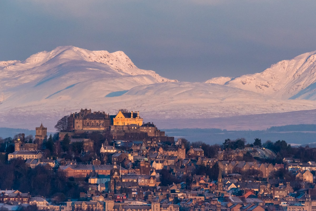 Stirling Castle in winter. The castle sits on a hill with snowy mountains in the background.