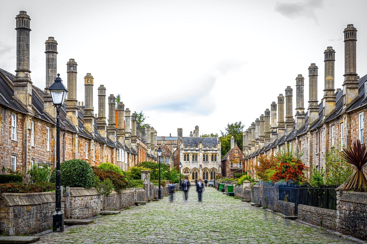 A view down the historic Vicars' Close in Wells. Old stone buildings line a cobbled road.