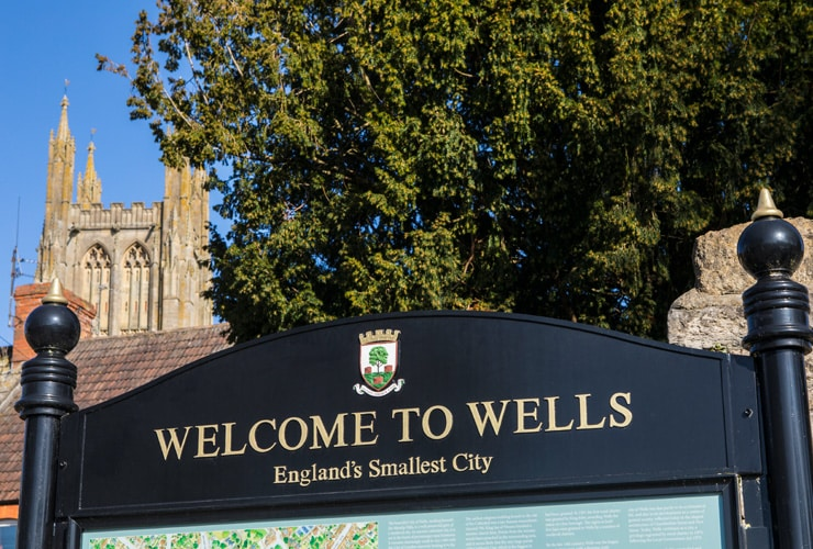 """Sign says, """"Welcome to Wells, England's Smallest City""""."""