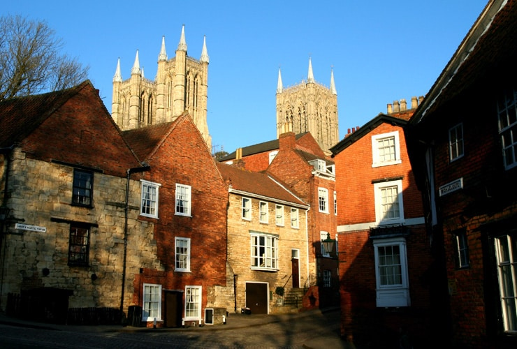 Medieval Streets of the City of Lincoln, Lincolnshire, UK, with the towers of the Cathedral above the ancient buildings, near sunset.