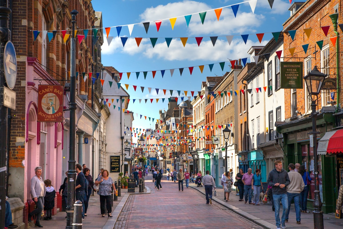 Shoppers wander the high street in Rochester with bunting overhead.