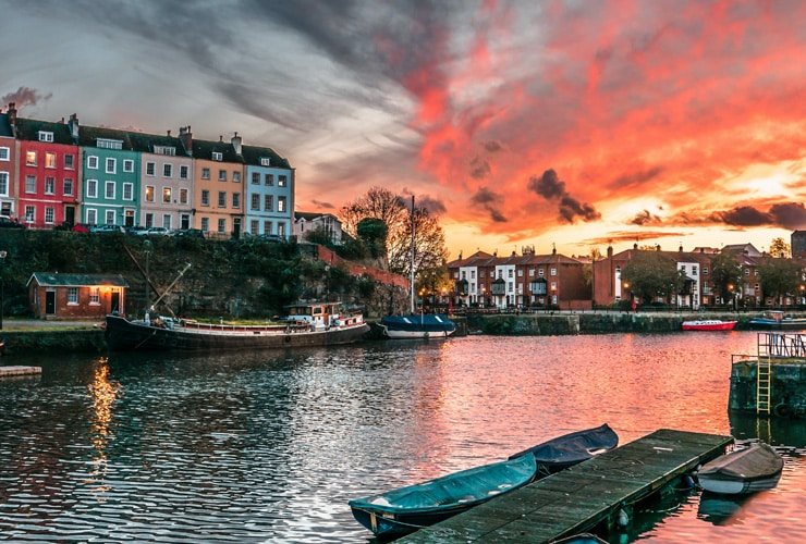 Bristol harbour at sunset with brightly coloured residential buildings in the background.