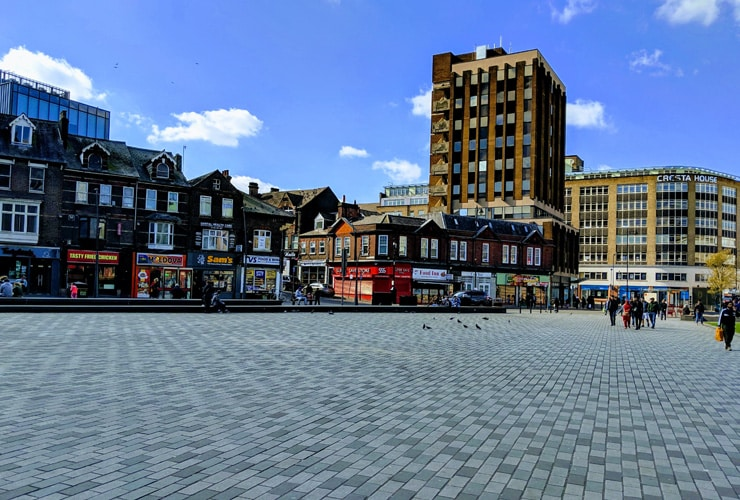 St George's square in Luton on a sunny day with tourists, shoppers and people walking.