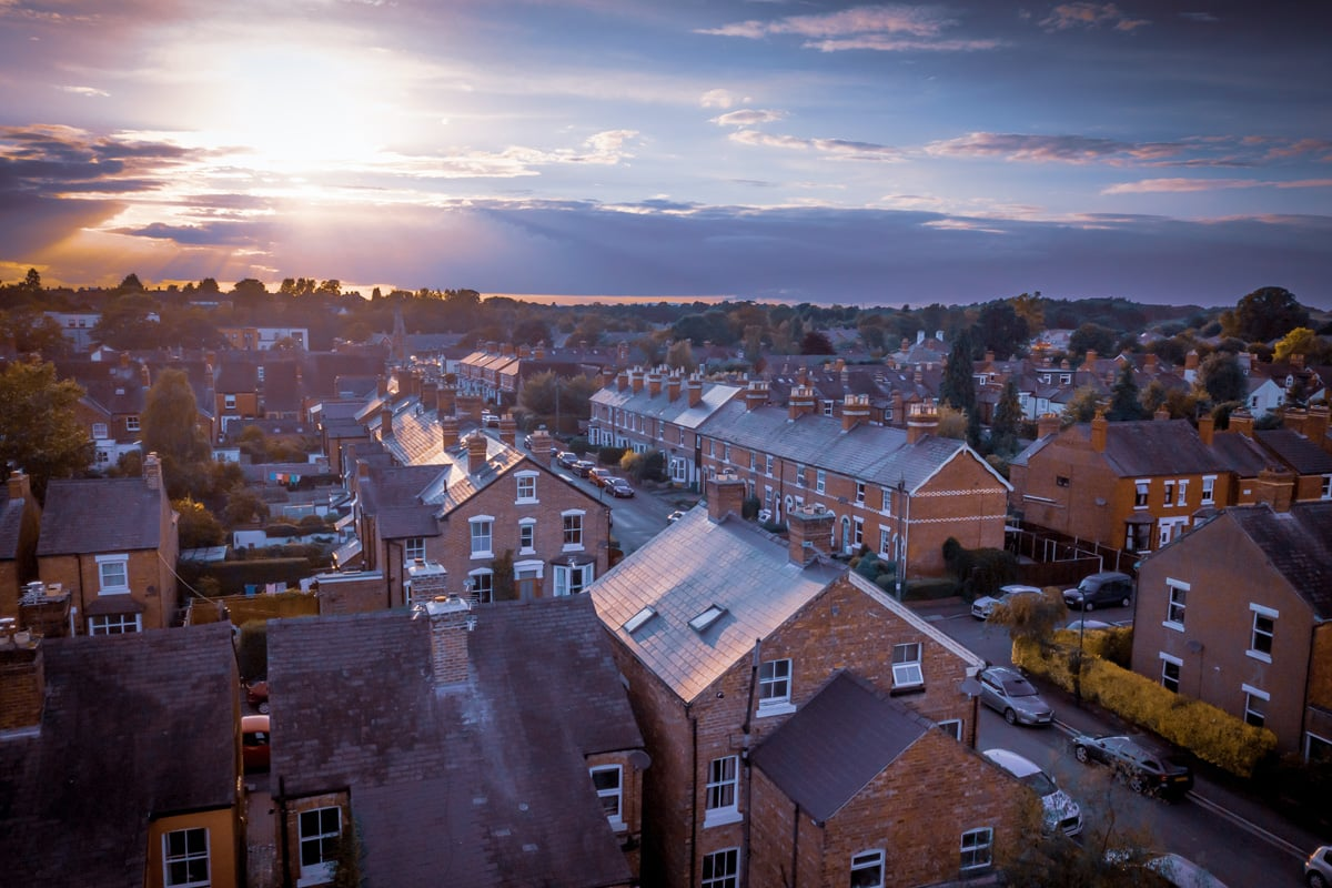 Sunset over traditional British houses with countryside in the background.