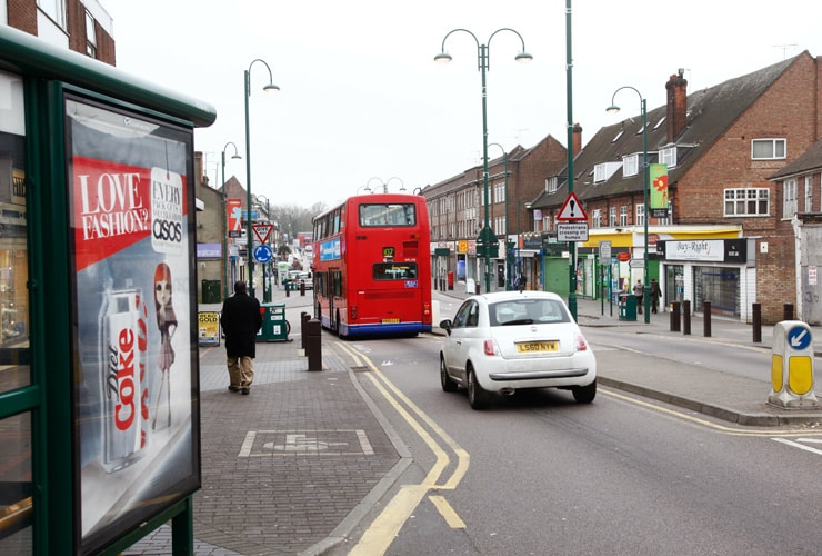 A red bus drives down a busy high street. Photograph taken in Borehamwood on the outskirts of London.