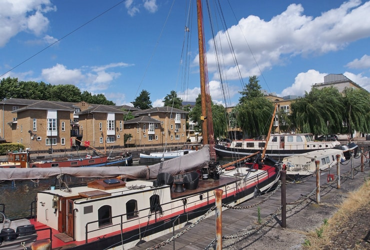 Canal boats with residential houses in the background. Photograph taken near Deptford.