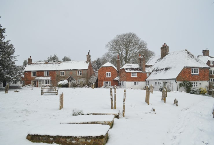 A photograph of hellingly church grounds and cottages under deep snow. The grounds are near Hailsham in East Sussex.