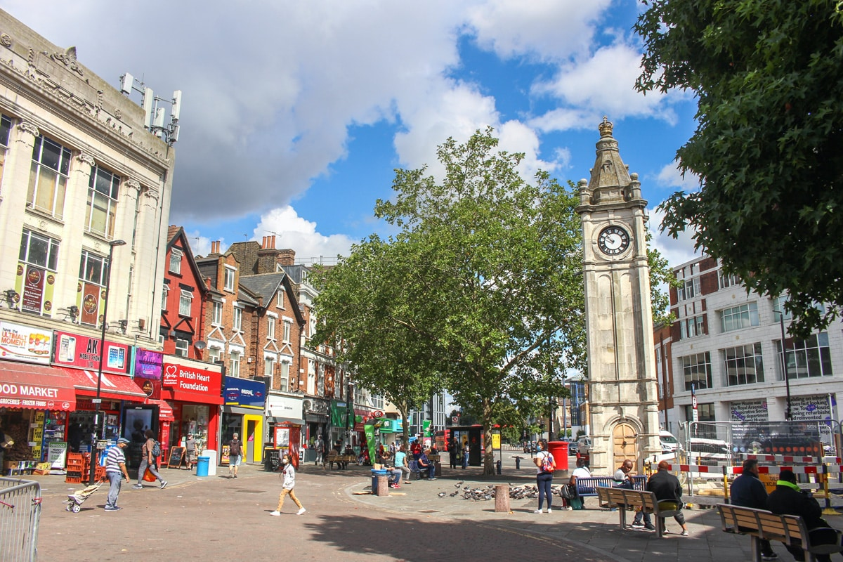 Lewisham high street on a sunny day. There are shoppers and the historic clock tower is in view.