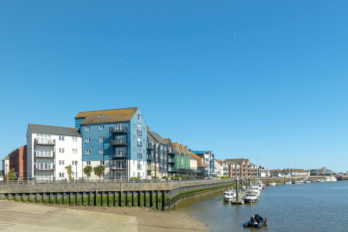 Residential blocks of flats sit alongside a harbour in Littlehamptopn Bay, Littlehampton, West Sussex.