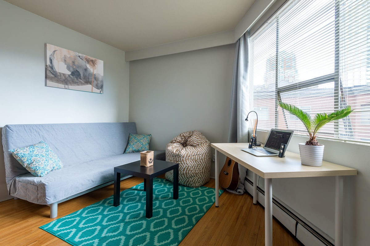 A room in a modern student apartment with a couch, a coffee table and a computer desk.