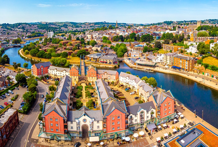 An aerial view of Exeter city along the river on a bright-blue day.