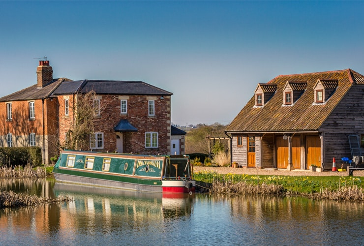 A canal boat is moored in front of a country house. Photograph taken in Devizes, Wiltshire.