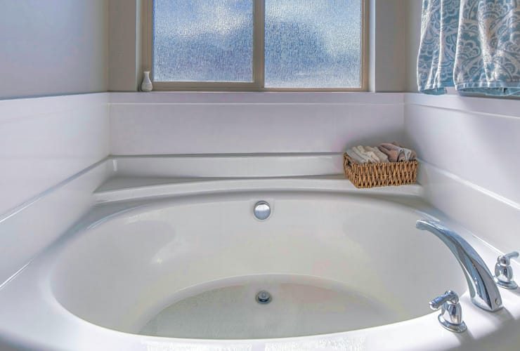A Pano Round built in bathtub with stainless steel faucet inside residential bathroom. A circular bath shape.