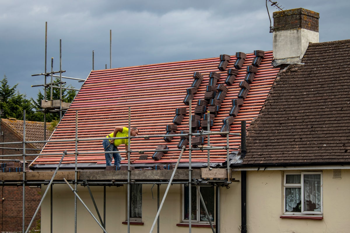 A man stands on scaffolding surounding a building. He is preparing to re-tile a roof.